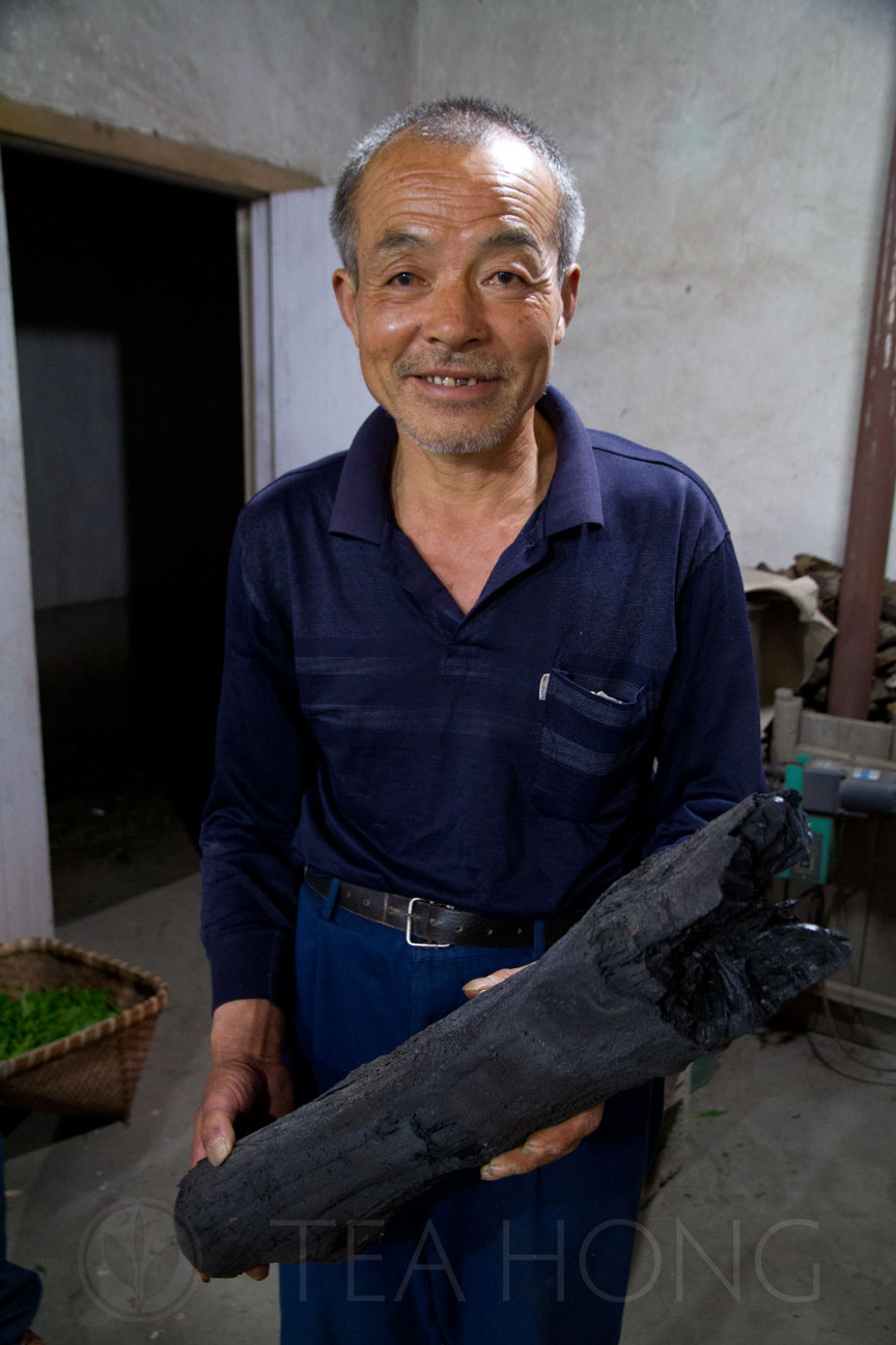 Master Wang holding a log of charcoal